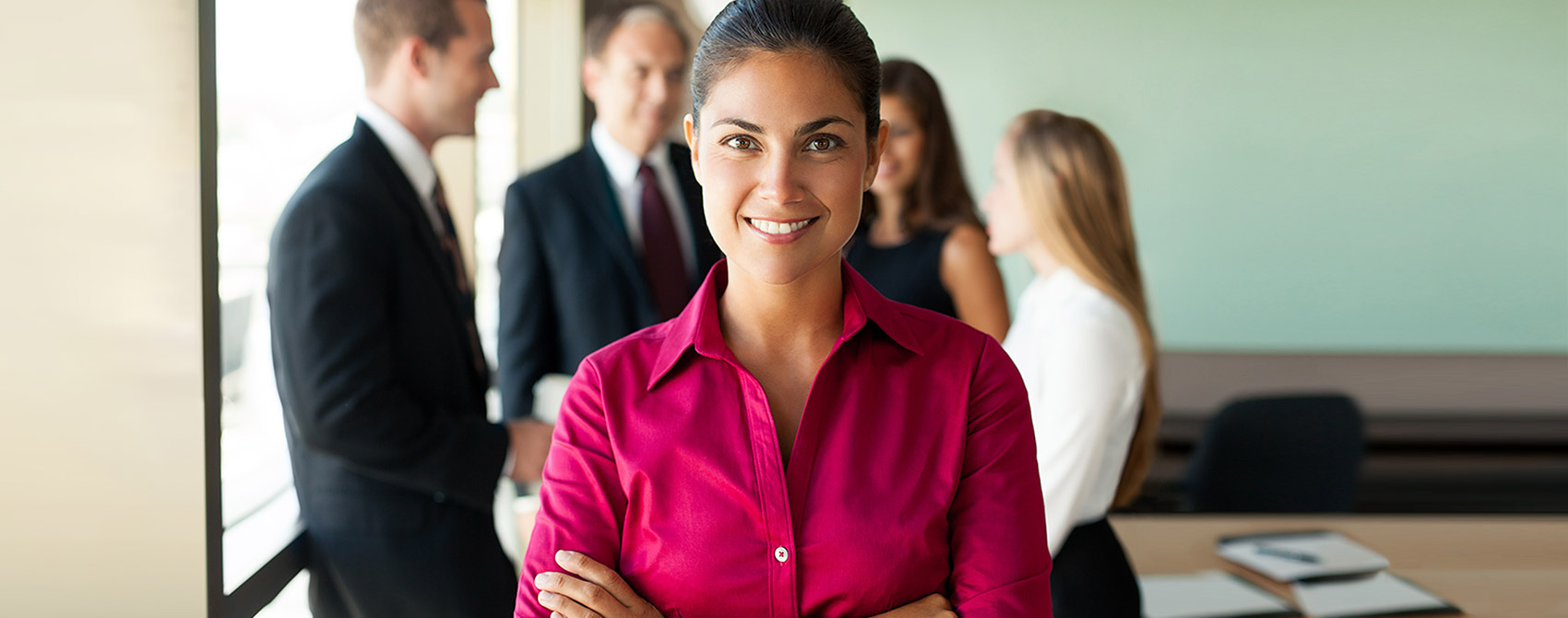 Confident female HR professional smiles at the camera while colleagues chat in the background.