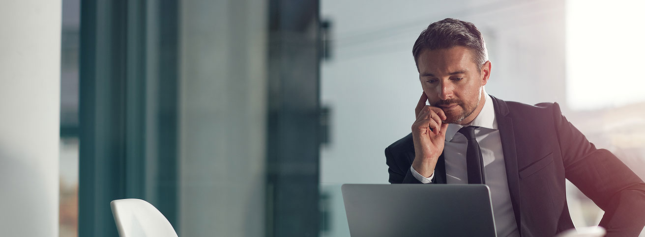 Business man in modern suit looks contemplative while looking at his laptop.
