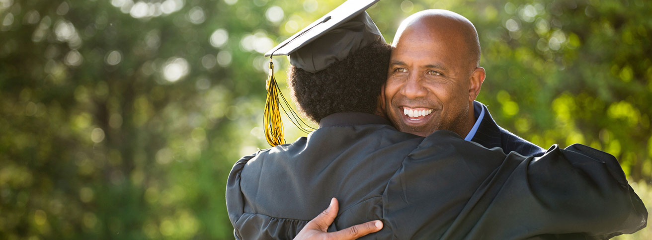 Father smiles while hugging son at his college graduation.
