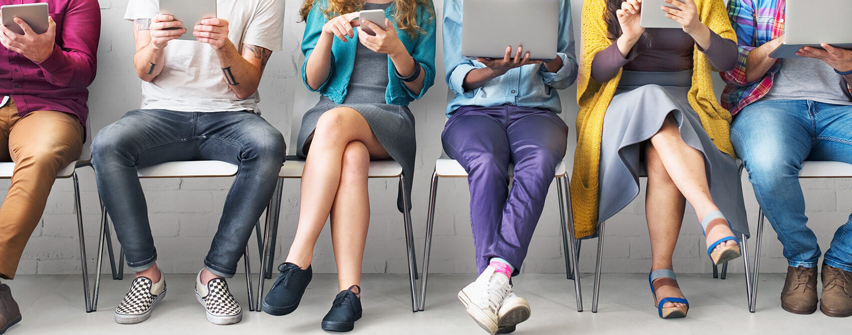 A group of people in modern outfits sitting next to one another use various electronic devices to access social and digital media.