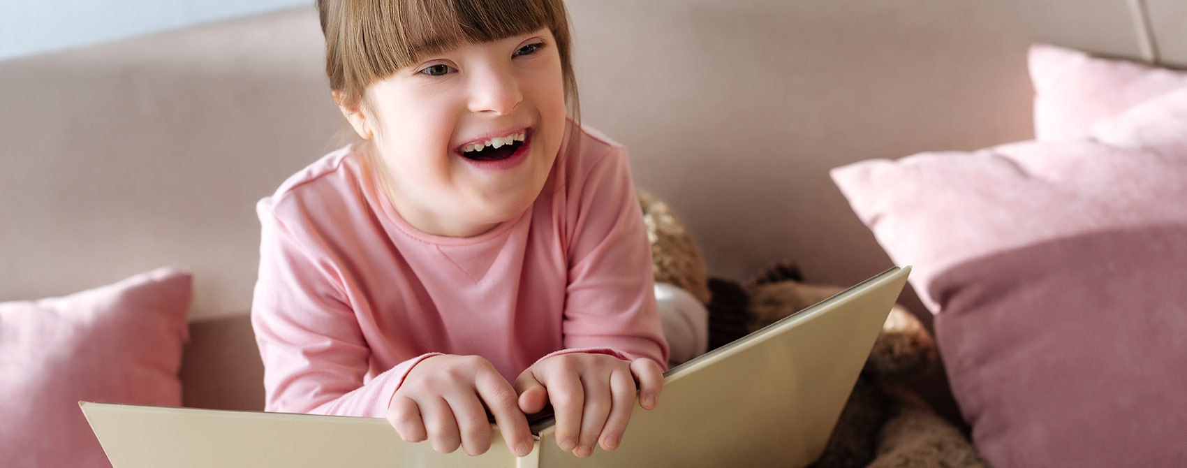 A smiling young girl with special needs holds an open book.