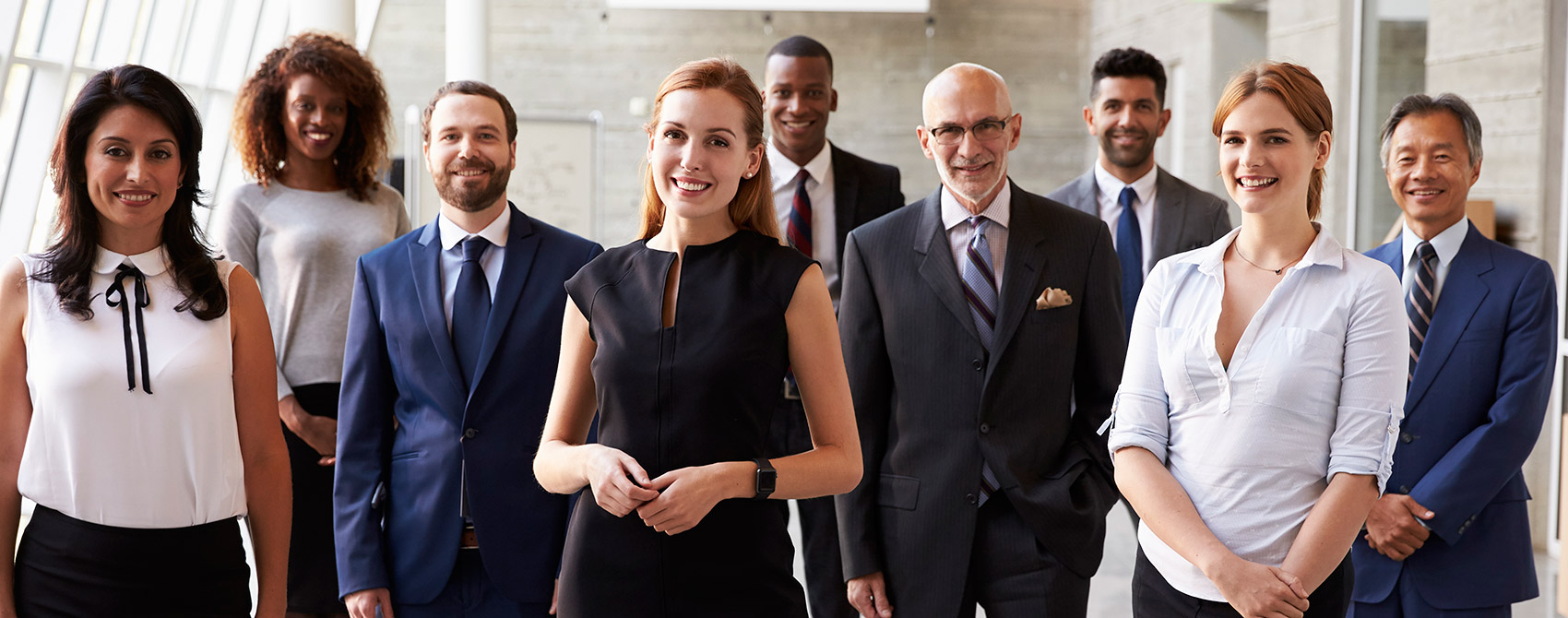Diverse group of communication professionals wearing business casual or suits pose together.