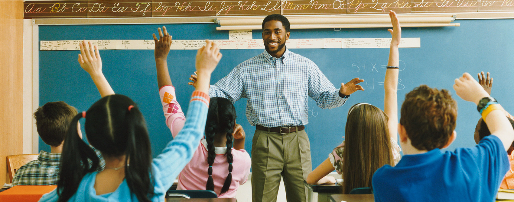 Math teacher stands in front of chalkboard with simple equations while class of diverse middle school students raise hands to answer the question.