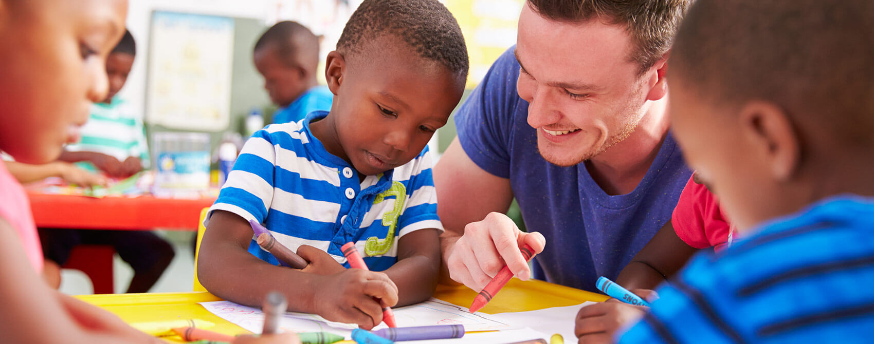 A young male teacher works with pre-k students who are coloring.