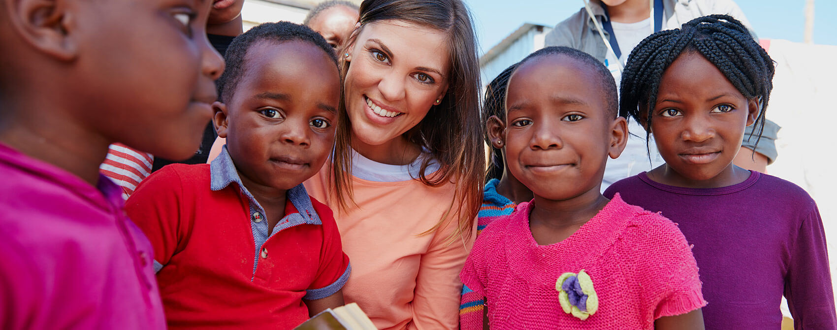 A female missionary posses with underprivileged children in a nondescript location.