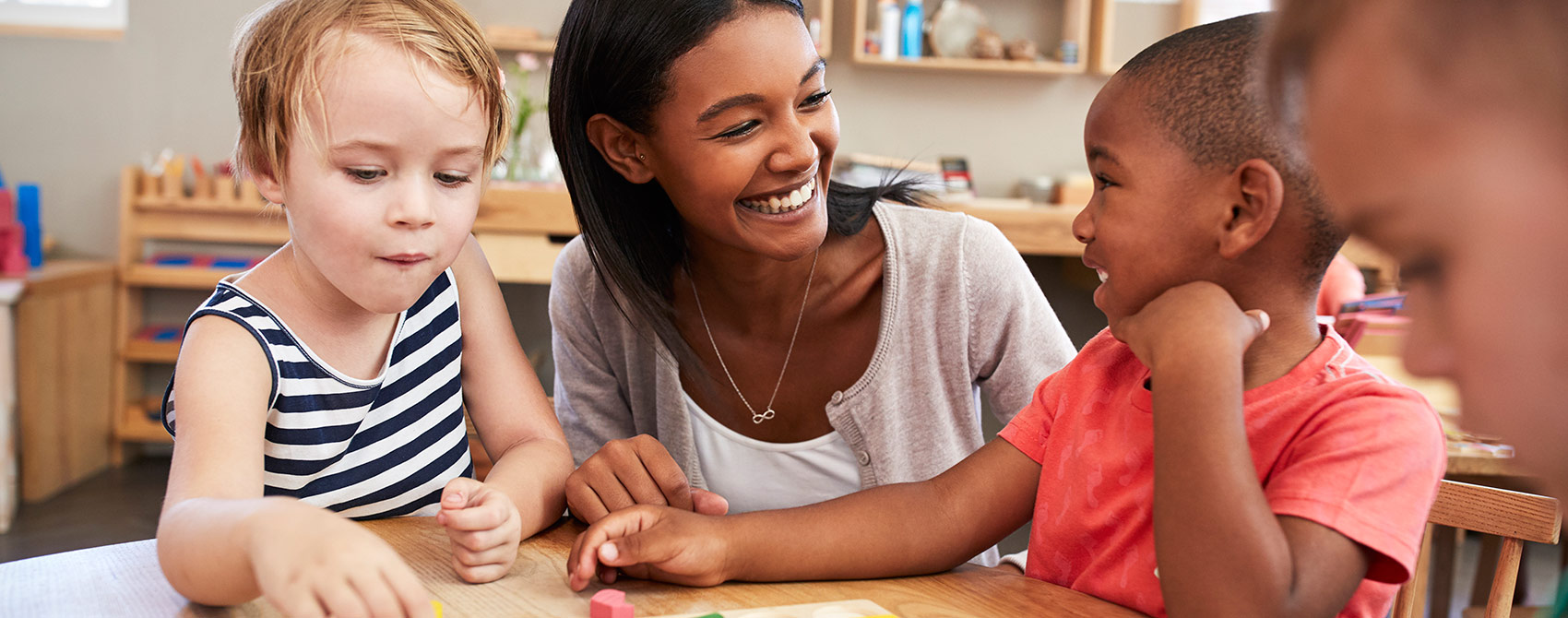 A Montessori teacher is smiling at her young students who are collaborating.