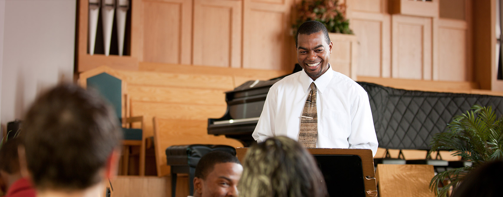 Minister standing at podium on stage in a church shares a smile with his parishioners.