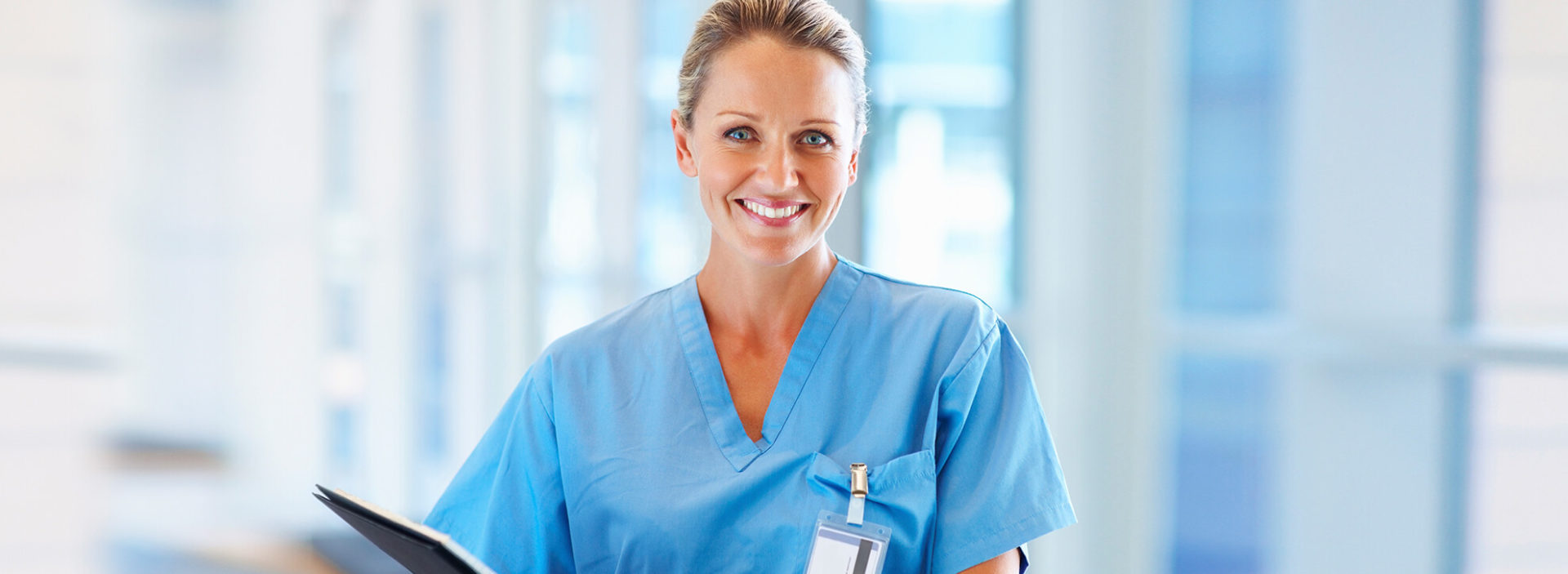 Nurse in scrubs smiles at the camera.