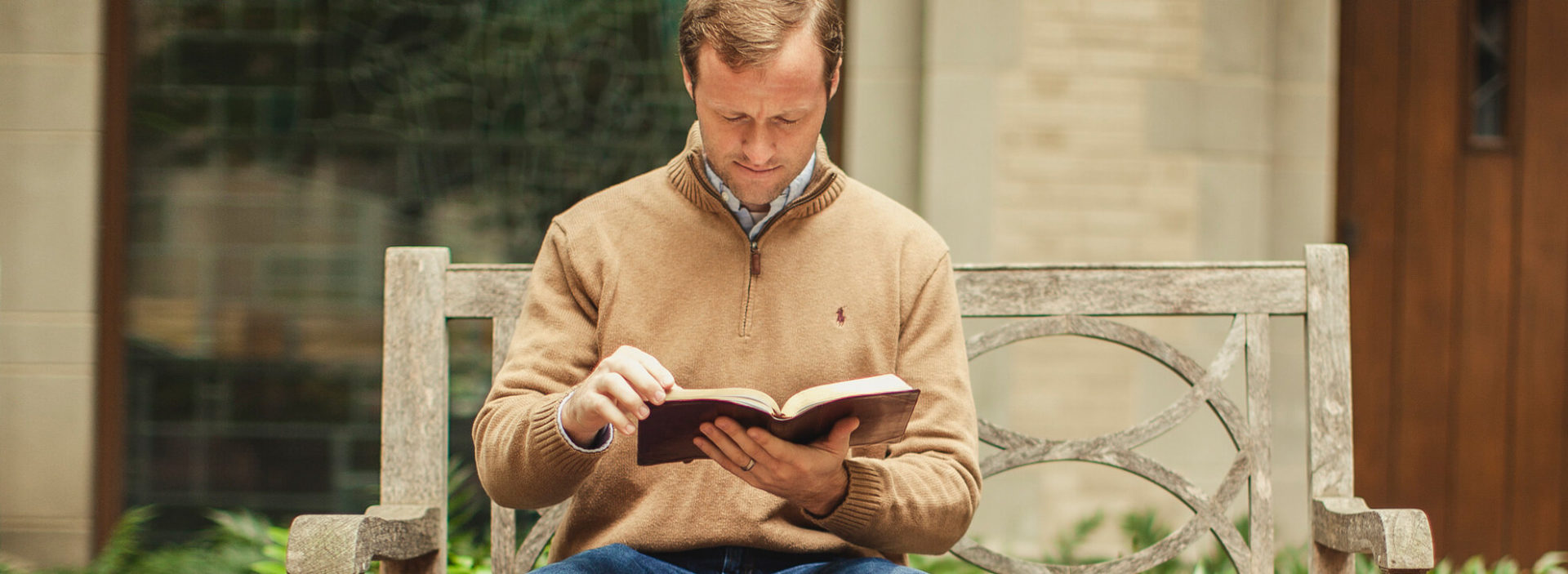 Adult man sits alone studying the bible on a bench in front of a church.