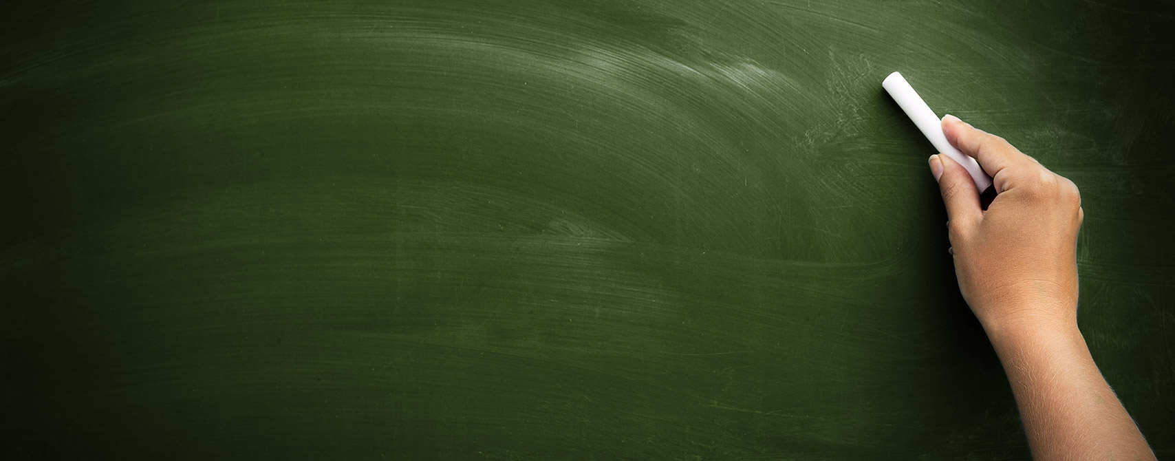 Freshly wiped green chalkboard with hand and chalk poised to write.