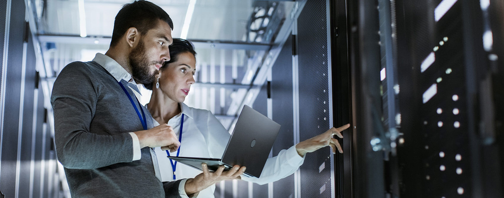 Information technology professionals examine a computer server. The male is holding a laptop, and the female is gesturing at the server.
