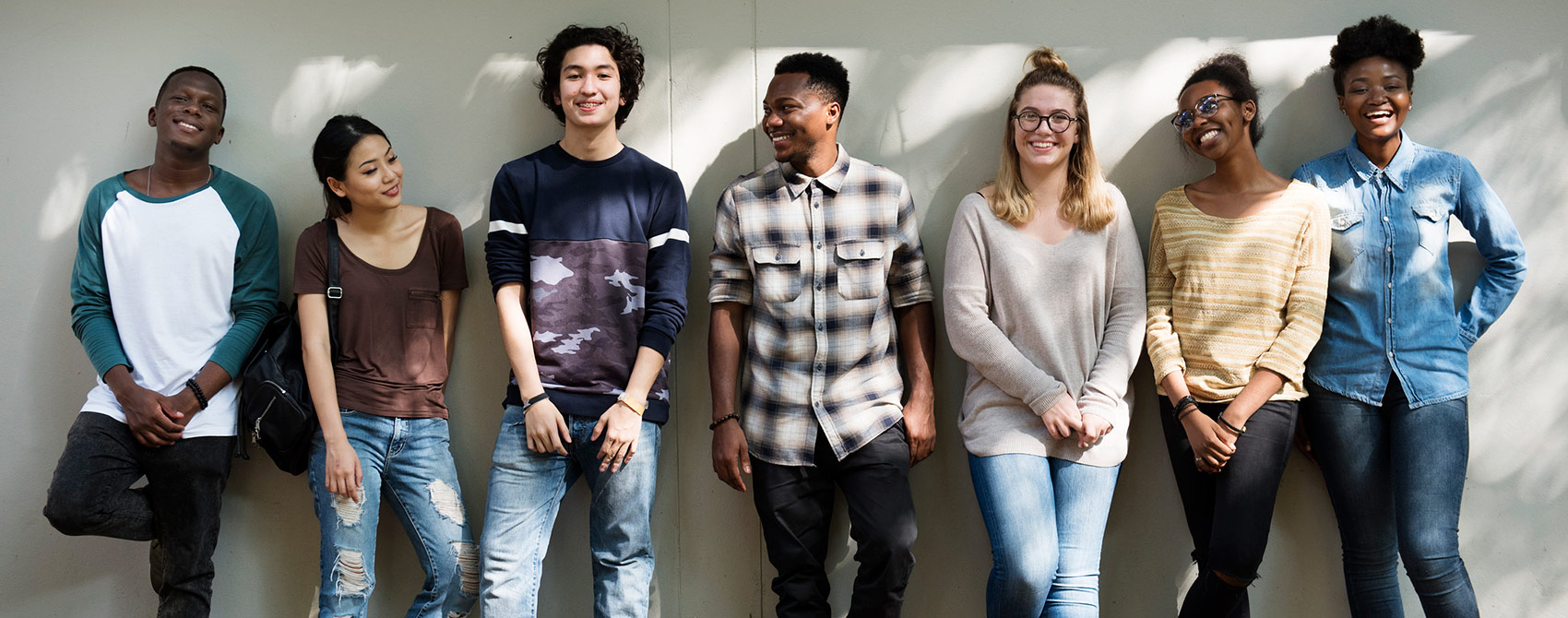 A group of collage students in casual clothes laughing together.