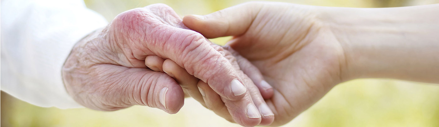 A social worker lightly holds the hand of an elderly client.