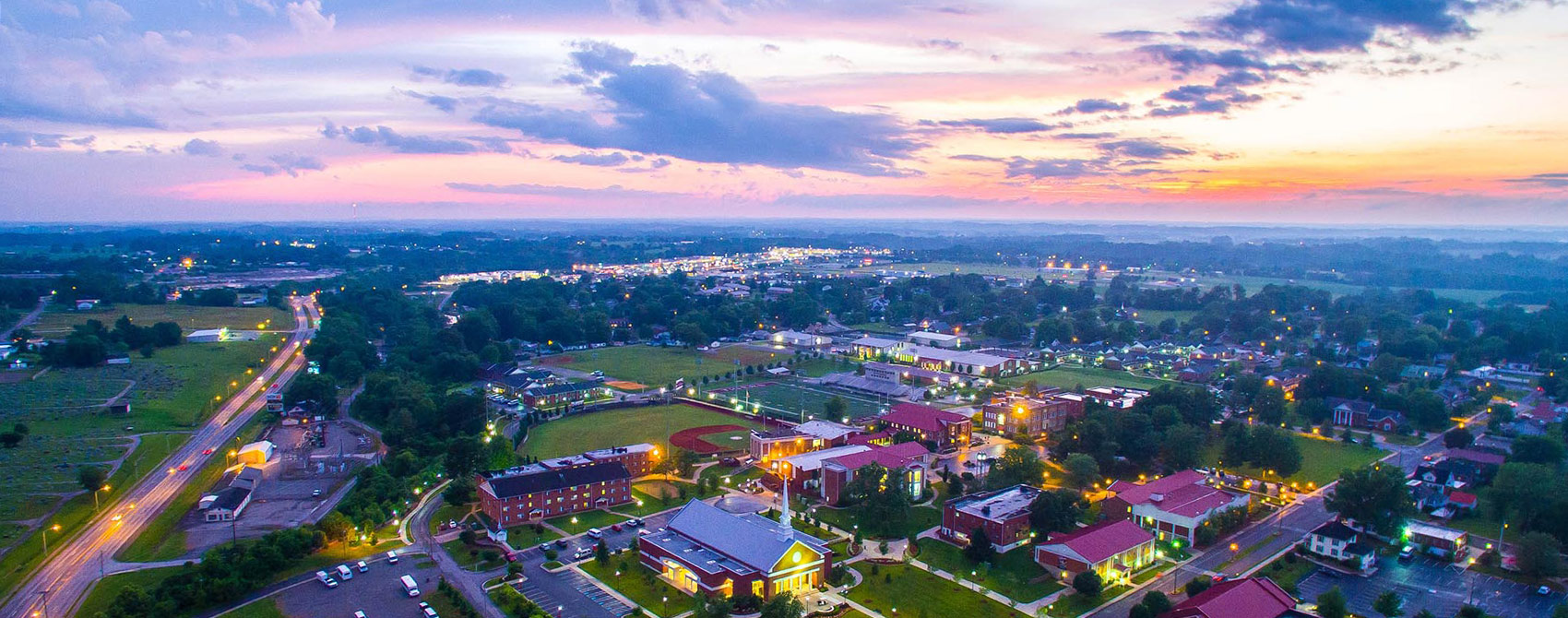 An arial photo of Campbellsville University's campus at dusk and the nearby busy road.