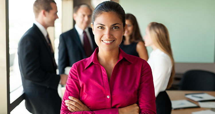 Female in business attire smiles with her arms folded while colleagues talk in the background.