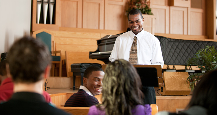 Young man ministers to his congregation in a church with pews and a piano.