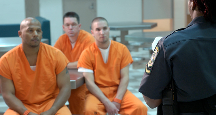 Three male inmates wearing orange receiving instructions from a prison guard.