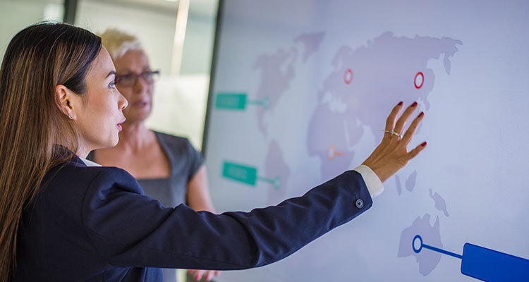 Woman in business attire gesturing to a digital world map with markup, explaining strategy to another business woman.