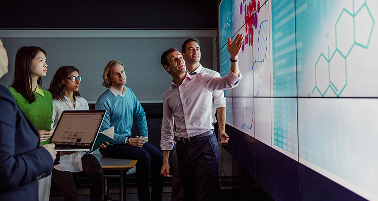 Man wearing business casual explains medical biotechnology product plans to colleagues on a large wall screen.