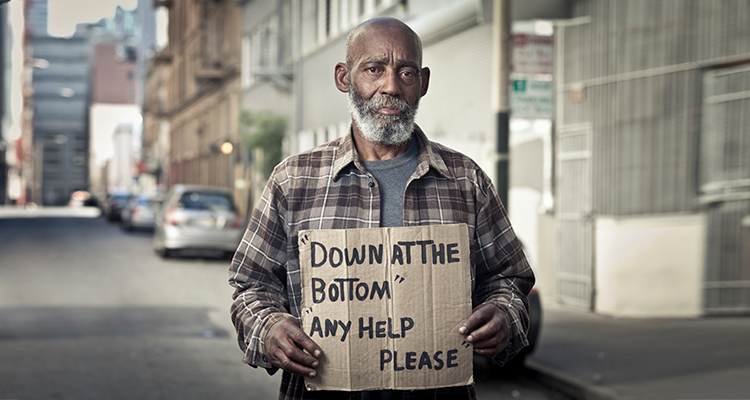 Photo of homeless African American man in a gentrified neighborhood holding a cardboard sign.