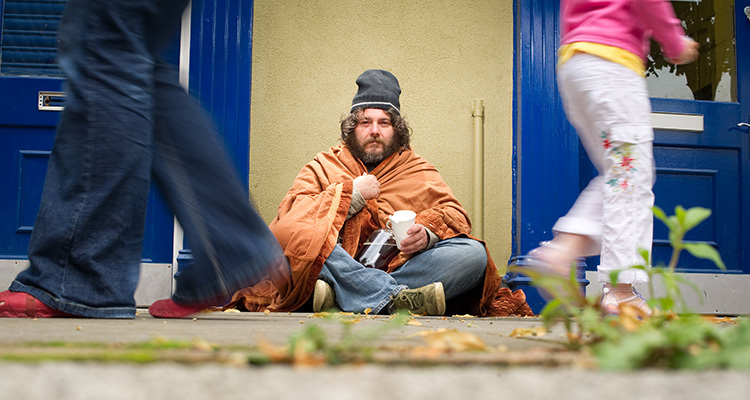 Man with unkempt hair and beard sitting on sidewalk in a blanket and jeans begging for money.