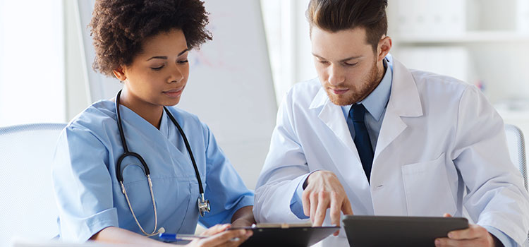 Female nurse in blue scrubs discussing patient chart with male doctor in white coat.